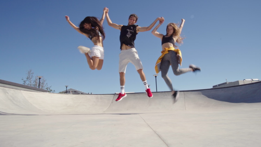 Urban friends at skate park posing for a photograph. Group of man and women crouching down and looking at camera smiling. Man starting the camera timer and running to the girls, crouching and posing