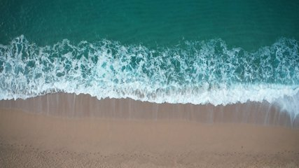 Drone view of beautiful seamless never ending footage while turquiose sea waves breaking on sandy coastline. Aerial shot of golden beach meeting deep blue ocean water and foamy waves