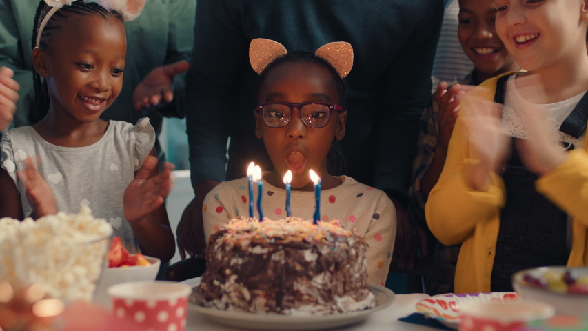African american birthday girl blowing candles on cake making wish celebrating party with friends children having fun celebration at home 4k footage | Shutterstock HD Video #1033912085