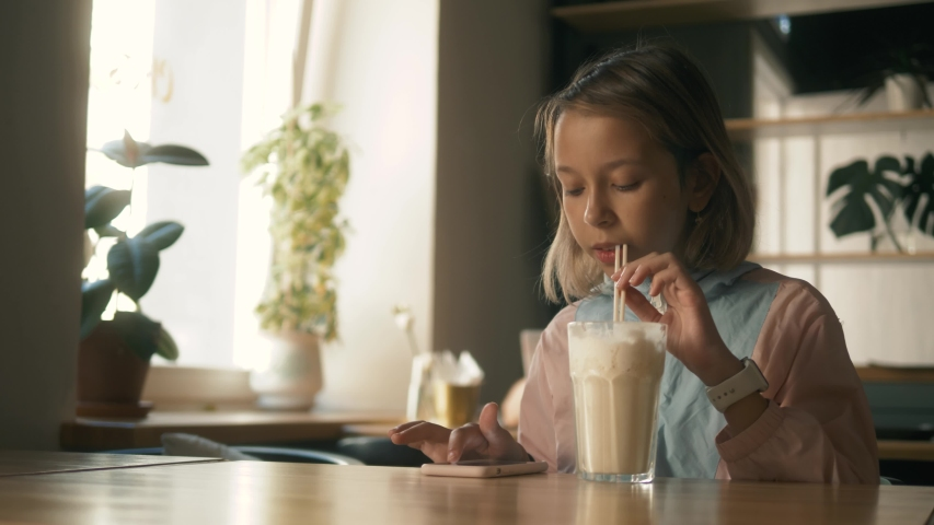 Beautiful girl in sitting in cafe counter and drinking milkshake while taking cute photos on her cellphone, child kid after lessons with cellphone | Shutterstock HD Video #1034002895