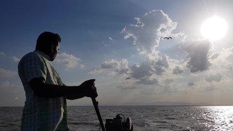 Irukkam Island, Andhra Pradesh / India - July 22 2019: Wide angle view of a boat man driving a motorboat with dramatic sky and clouds in the background