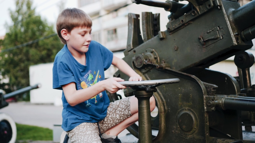 The boy sits on the anti-aircraft installation and turns the controls. Cool footage. Children's education and development. | Shutterstock HD Video #1034085845
