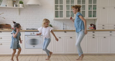 Happy family active young mom and two cute small children dancing jumping together in kitchen, carefree funny little daughters copy imitate mother baby sitter having fun do exercises laughing at home