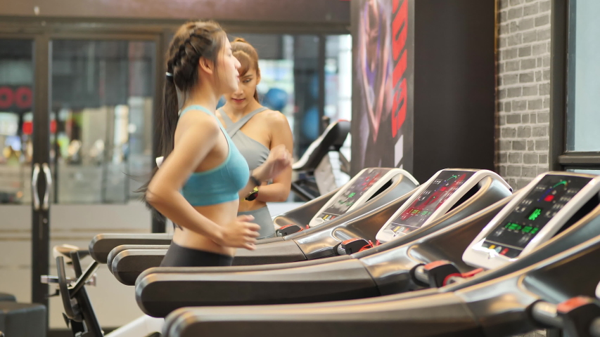 Two Young women running on a treadmill and trainer helped guide at gym. Fitness and healthy lifestyle concept.  | Shutterstock HD Video #1034135735