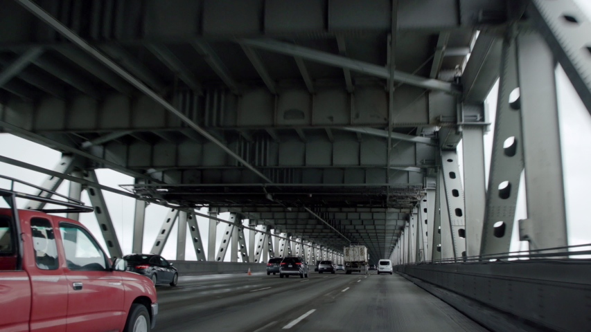 POV of cars driving on a bridge has a stark, futuristic look as they move forward in this smooth camera shot on a gimbal.  Filmed in 4K on a Canon C200.