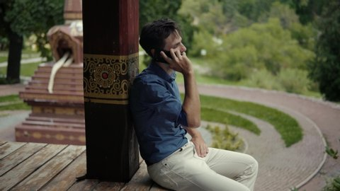 Businessman Using Mobile Phone At Beautiful Place.Handsome Bearded Man Talking By Smartphone.Man Talking On Mobile Phone.Young Attractive Bearded Man Sitting And Talking On Mobile Phone With Friend.