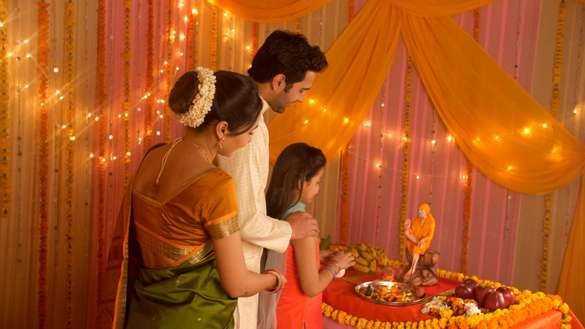 Indian nuclear family worshiping Indian Spiritual Master Sai Baba during festivities. HD stock video of Indian family following Hindu customs and traditions during festivities - Offering prayers. G...