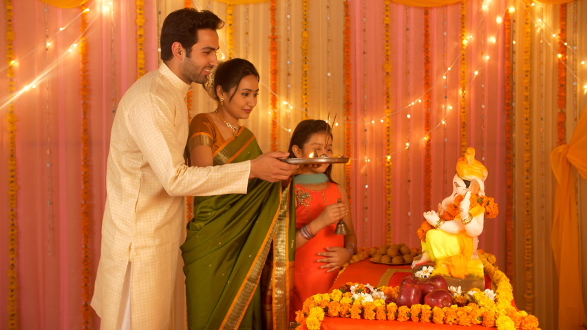 Beautiful Indian family worshiping Lord Ganesha during festivities - Puja and Aarti. Indian stock video of a nuclear family celebrating the festival of Ganpati Puja at home - Strong family bond and...