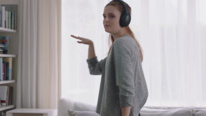 Happy woman dancing at home having fun listening to music wearing headphones enjoying weekend celebration with funny dance moves | Shutterstock HD Video #1034231345