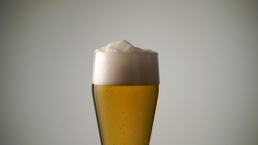 Full glass of beer with foam and rising bubbles close-up   Shutterstock HD Video #1034309795