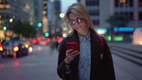 Young millennial travel blogger typing content text for publication with information about touristic benefits of visiting metropolitan city, smiling woman in eye spectacles using cellular device