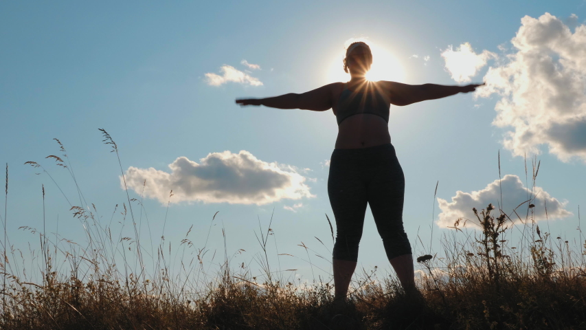 Silhouette: Plus size woman doing sport exercises on grass spending time in highlands in the morning. Slow-motion video
