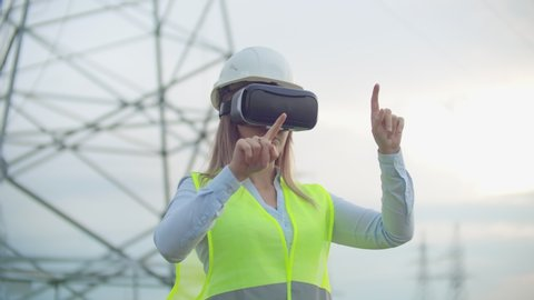 High-voltage power lines controlled by a female engineer using virtual reality to control power. Alternative energy sources in a modern city.