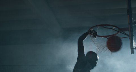 Cinematic slow motion shot of an young african professional male player is making a  slam dunk during a basketball work out in a gym.
