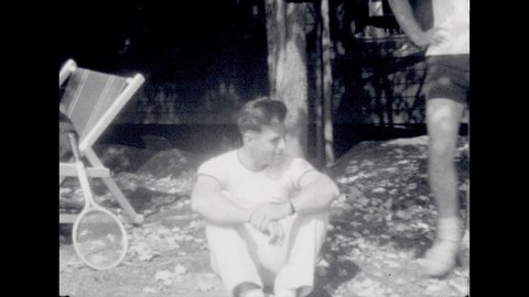 1940s: Elderly and younger men sit. Elderly man talks to camera. 2 women sit, talk on bench. Young woman talks. Older lady sews on lawn chair. Man talks. Man with pipe waves, walks. Lady, boy garden.