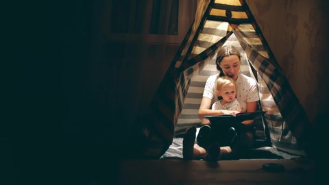 Mum and her little daughter read a book together in a teepee in the evening