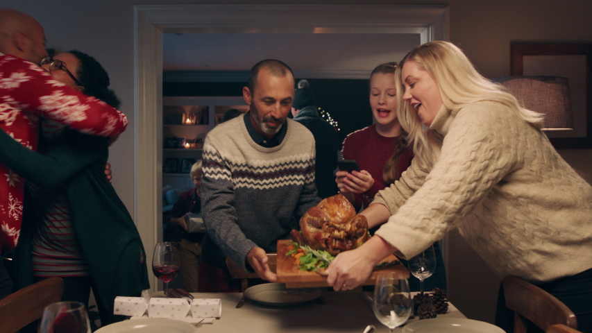 Christmas family preparing dinner table with turkey friends arriving for dinner party celebrating festive holiday reunion enjoying feast at home 4k footage