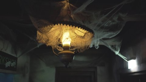 Old style vintage blinking lamp full of artificial spider net in a dimmed scary room