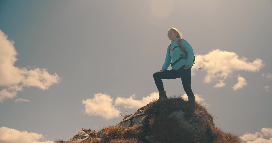 Woman tourist traveler walking on the top of mountain in summer sunny day under sun light. Beautiful mountains landscape view. 4K slow motion video
