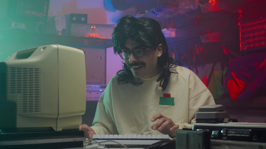 Happy computer nerd in the '80s or '90s using his personal computer. Retro scene with vintage colors and atmosphere. | Shutterstock HD Video #1034714285