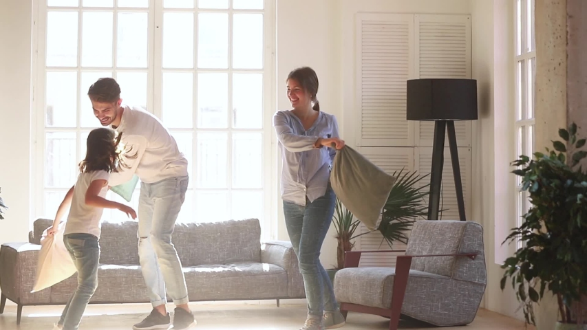 Cheerful young full family with small preschool daughter holding cushions having fun together in light cozy modern living room playing fight with pillows, laughing enjoy active weekend at home concept | Shutterstock HD Video #1034755955