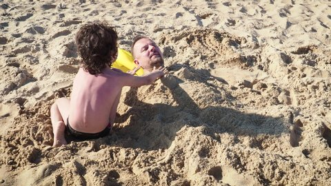 4K Father Plays With His Little Boy At Beach, Little Son Is Buried In Sand, Cute Moment Slow Motion