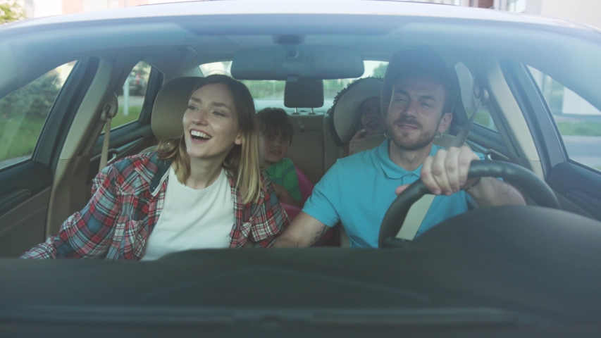 Front view of happy loving parents and their excited kids smiling driving a car in the city. Young family traveling abroad by car in summer. | Shutterstock HD Video #1034878295