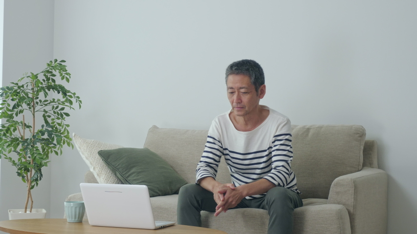 Middle aged asian man having a low back pain. | Shutterstock HD Video #1034910395