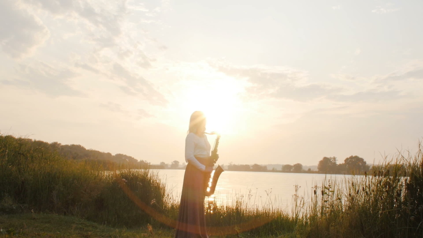Silhouette of a young woman playing on the saxophone near the riverbank at dawn, a beautiful girl in a long dress with a wind musical instrument in nature, a concept of hobby and relaxation | Shutterstock HD Video #1034984435