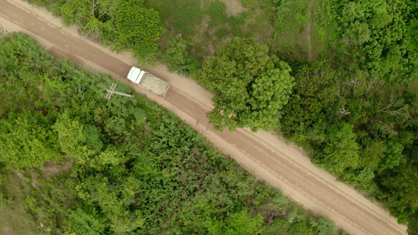 Two shot. Aerial view, construction truck is transporting materials through a dirt path surrounded by trees. Activity machine in building business. Top view from drone. Rotate camera. #1035018935
