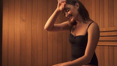 Leisure activity concept.Profile and side view of charming, sweet and gorgeous young woman sitting on wood bench inside small wooden sauna cabin, breathing hot air ang making lovely calm smile