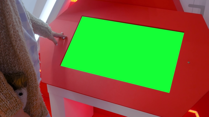 Woman looking at blank digital interactive green display kiosk at exhibition or museum with futuristic sci-fi interior. Mock up, copyspace, template, chroma key, green screen, technology concept   Shutterstock HD Video #1035027785