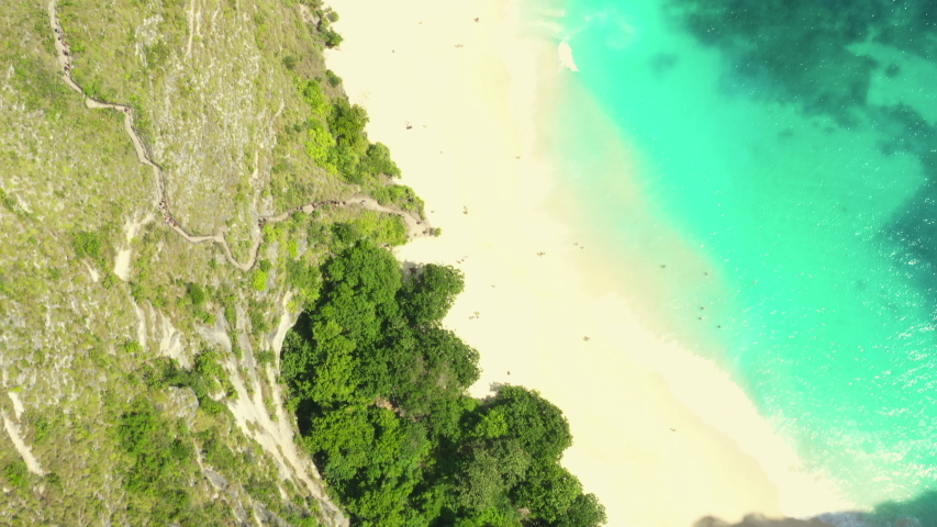 Aerial view of Kelingking beach, Nusa Penida, Indonesia with danger hiking trail on the top of mountain leading to amazing sandy beach with azure clear sea water. 4k | Shutterstock HD Video #1035052535