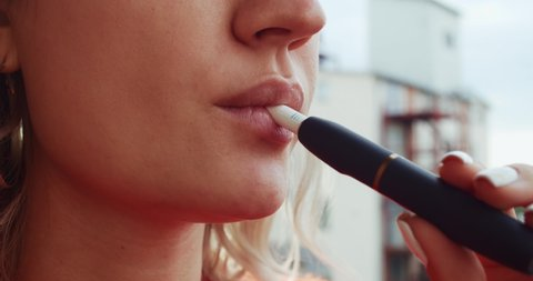 Close-up pretty woman with electronic cigarette outdoors. Young woman smoking tobacco stick heating and exhailing smoke.