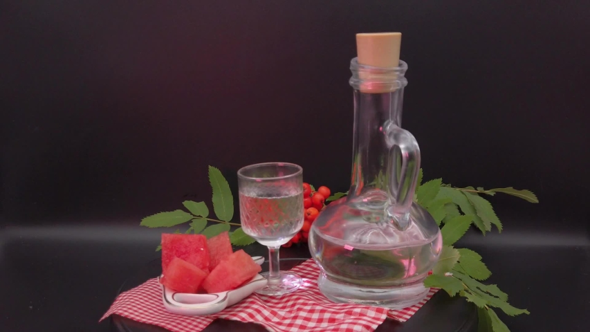 Vodka in a decanter and a stack, watermelon slices slowly rotate. | Shutterstock HD Video #1035147425