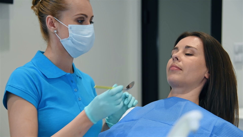 Woman Patient With Open Mouth During Oral Checkup In Dental Clinic | Shutterstock HD Video #1035168485