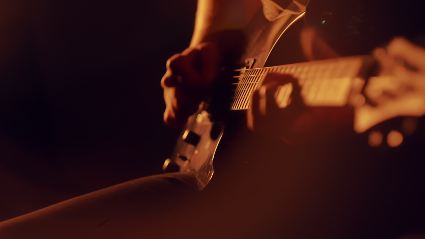 Human hands playing on electric guitar. Close up of rock musician playing guitar on stage with scenic illumination. Bassist playing electric bass guitar. Fingers on guitar strings | Shutterstock HD Video #1035197165