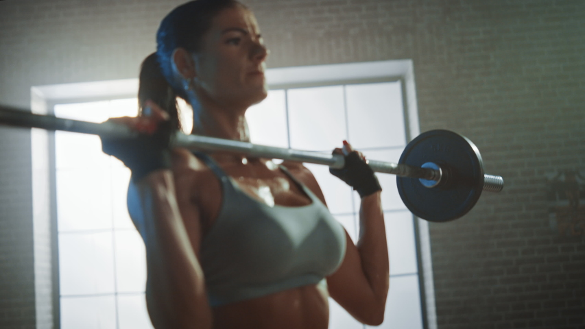 Athletic Beautiful Woman Does Overhead Deadlift with a Barbell in the Gym. Gorgeous Female Professional Bodybuilder Workout Weight Lift Exercises in the Authentic Fit Training Facility. Zoom in