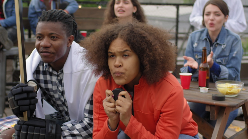 Excited African girl biting hockey puck and then yelling and celebrating winning of favorite team while watching match with friends in outdoor bar on urban rooftop | Shutterstock HD Video #1035267875