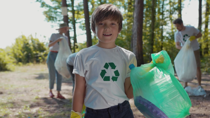 Happy boy voluteers activists child in gloves tidying up rubbish in park or forest look at camera smile  | Shutterstock HD Video #1035318245