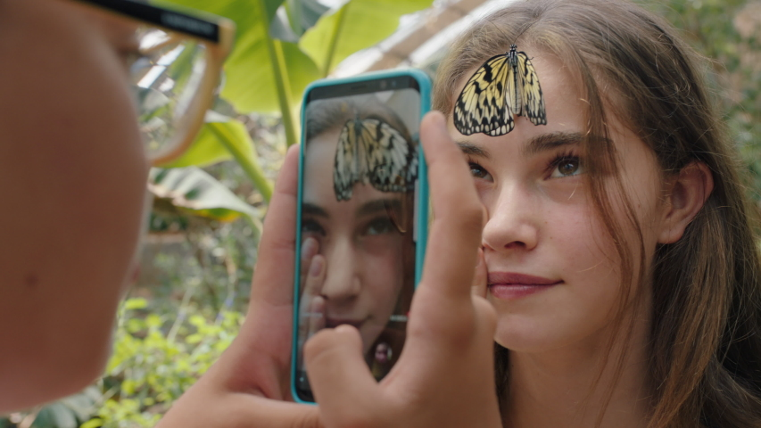 Beautiful butterfly on girls face with happy friend taking photo using smartphone friends having fun in zoo wildlife sanctuary sharing nature excursion on social media 4k footage | Shutterstock HD Video #1035354515