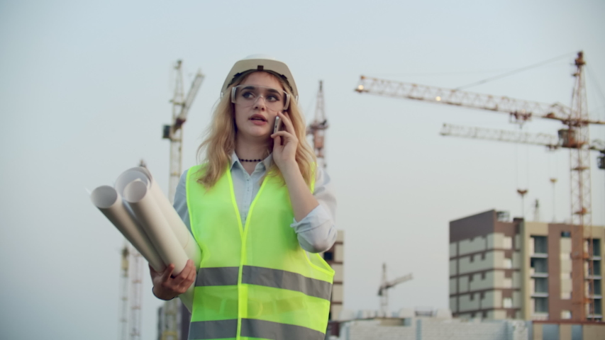 Portrait of a woman engineer in a helmet talking on the phone on the background of construction with cranes holding drawings in his hands. Female engineer on construction site | Shutterstock HD Video #1035360395