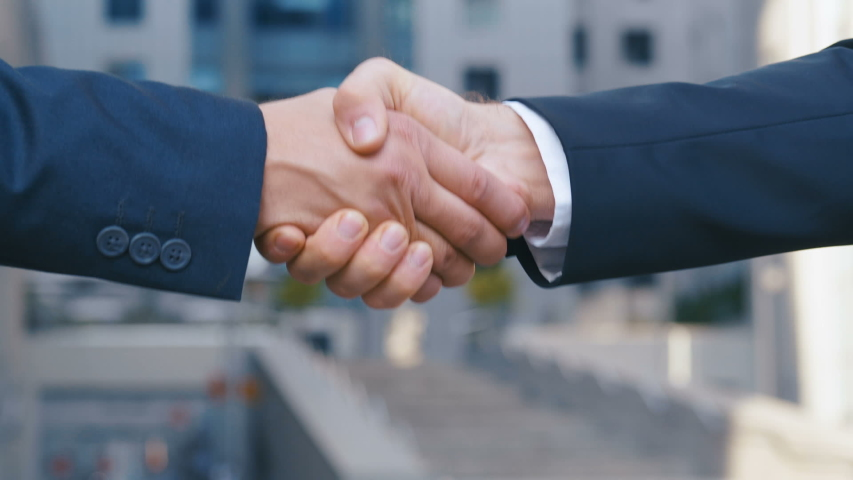 Close up of the hands of top managers in business suits, shake hands with each other, at Business center background, agree to a deal or say hello. Slow motion, unrecognizable person