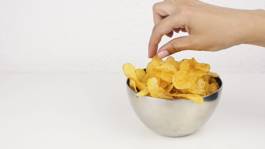 Female beautiful hands with take potato chips from a deep plate. Unhealthy food, fast food   Shutterstock HD Video #1035425375