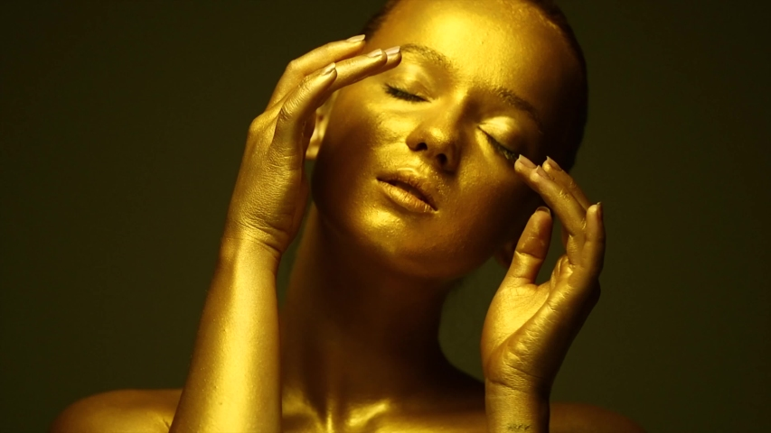 Fashion art Golden skin Woman face portrait closeup. Model girl with holiday golden Glamour shiny professional makeup. Gold jewellery, jewelry, accessories. Beauty gold metallic body, painted Skin 4K | Shutterstock HD Video #1035429665