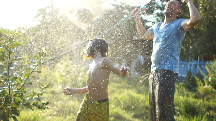 Father and son fooling around watering each other from a hose on a hot summer day. Holidays in the countryside, summer holidays