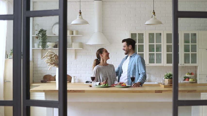 Happy loving young family couple cutting fresh vegetable salad having fun cooking together in modern cozy kitchen interior, smiling husband and wife bonding laughing helping prepare healthy meal | Shutterstock HD Video #1035500735