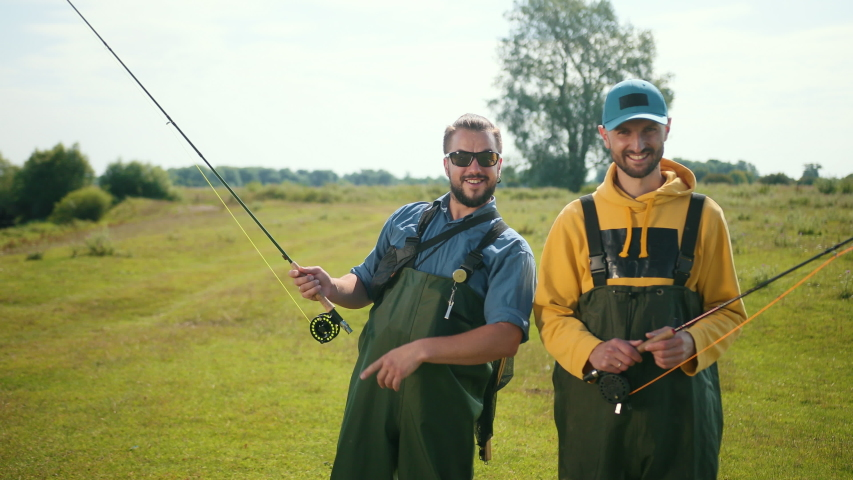 Two men fisherman, with black hair and beard, green overalls, holding a fishing rod and a float, communicate with each other, smile, on the street, by the river on the grass, Sunny weather, close-up | Shutterstock HD Video #1035537005