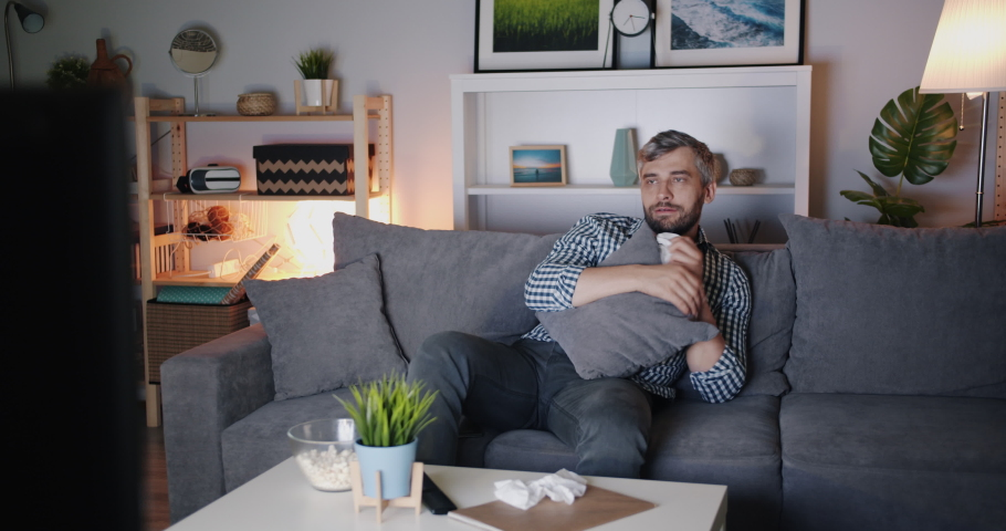 Bearded man is watching TV eating popcorn and wiping nose with tissue sitting on sofa in apartment alone. Modern technology, culture and emotions concept. | Shutterstock HD Video #1035539075