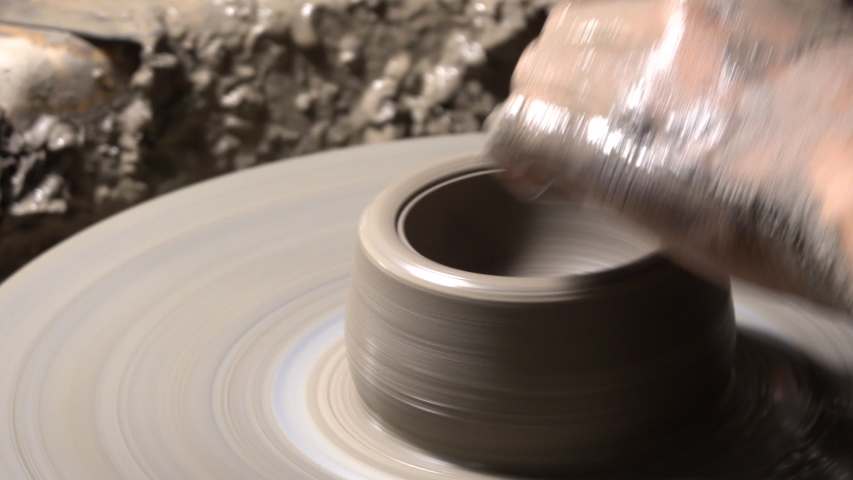 Close-up shot of a professional creating ceramic vase spinning on potters's wheel. | Shutterstock HD Video #1035559475